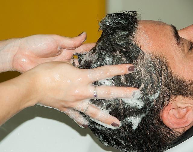 シャンプーで髪を洗う男性