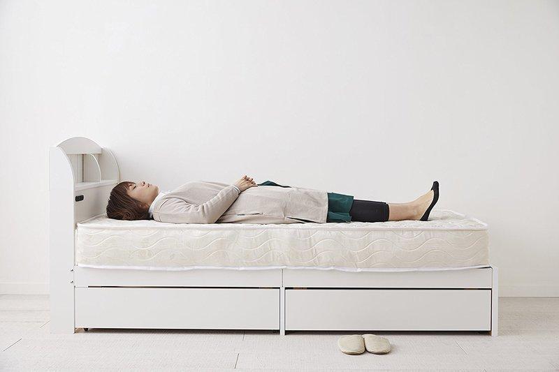ベッドマットレスに横たわる女性
