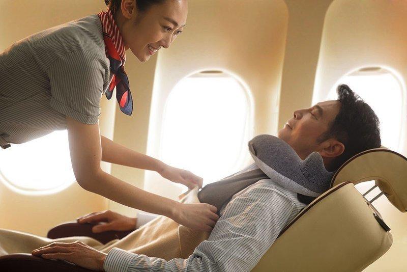 飛行機内でネックピローを装着して仮眠する男性