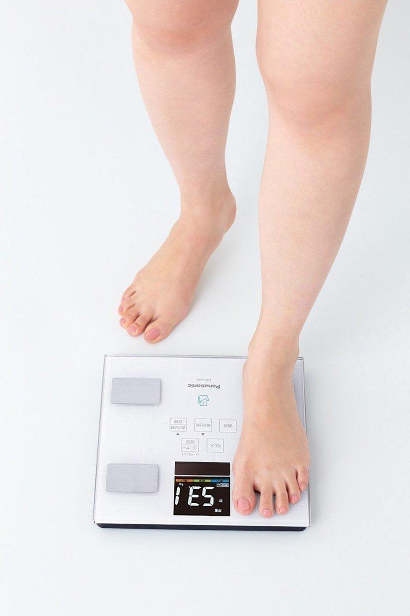 体組成計に足の乗せる女性