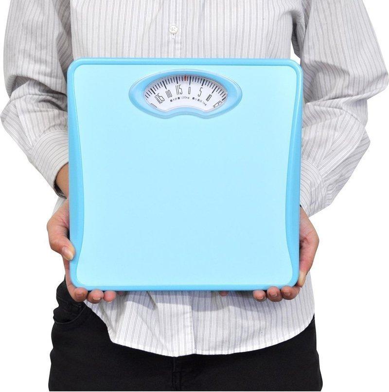 アナログ式体重計を手に持つ男性
