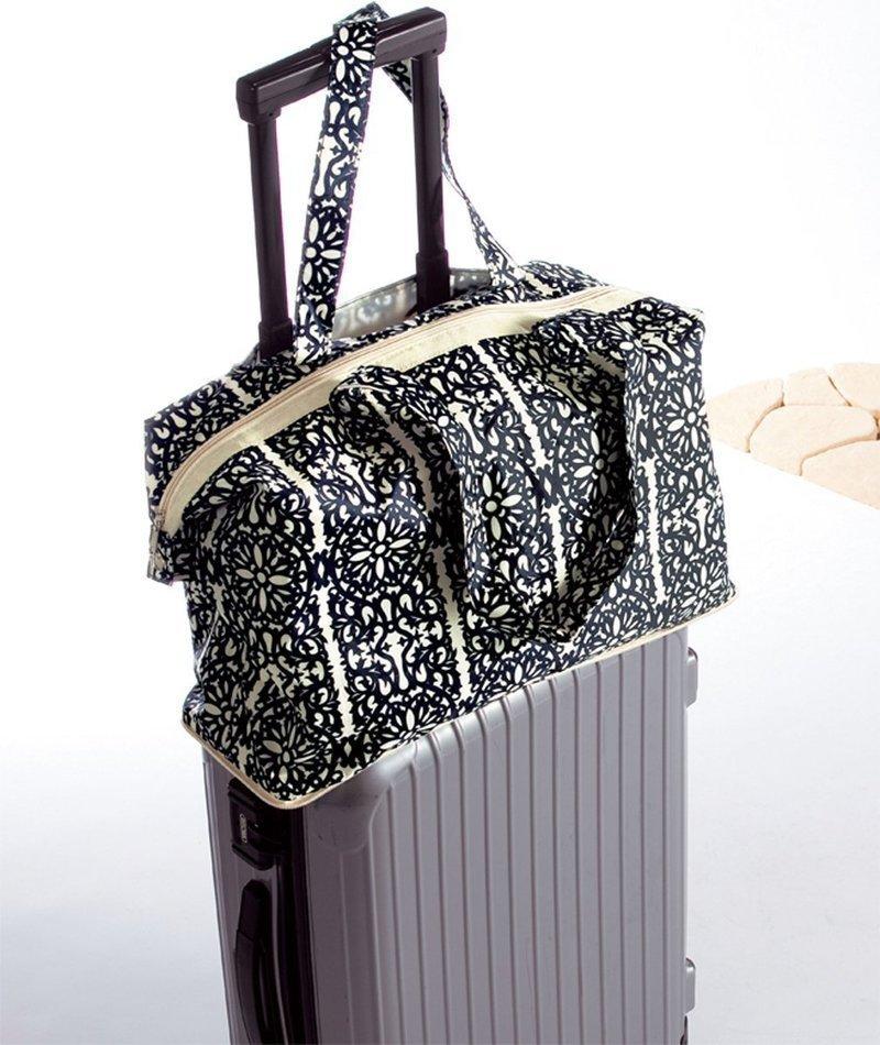 スーツケースの上に載せられたキャリーオンバッグ