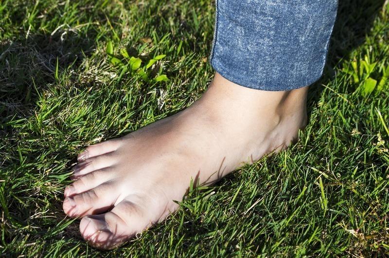 芝生の上に立つ男性の足