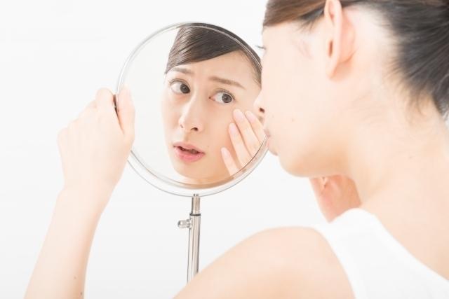 肌の乾燥を気にして鏡をチェックする女性
